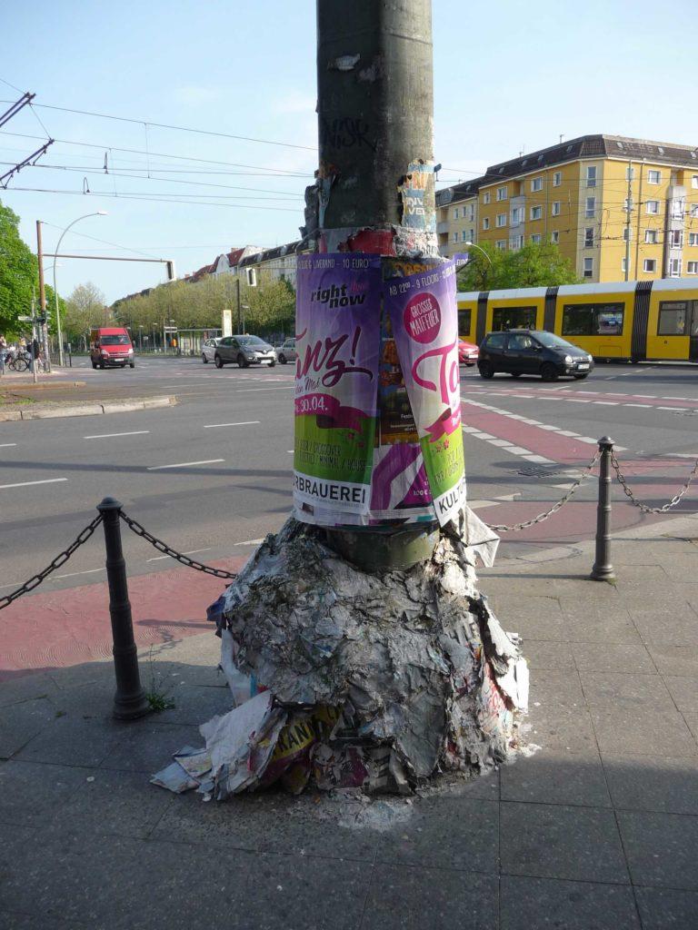 Laternenmast in Berlin, der vollkommen mit Plakaten zugeklebt ummantelt ist