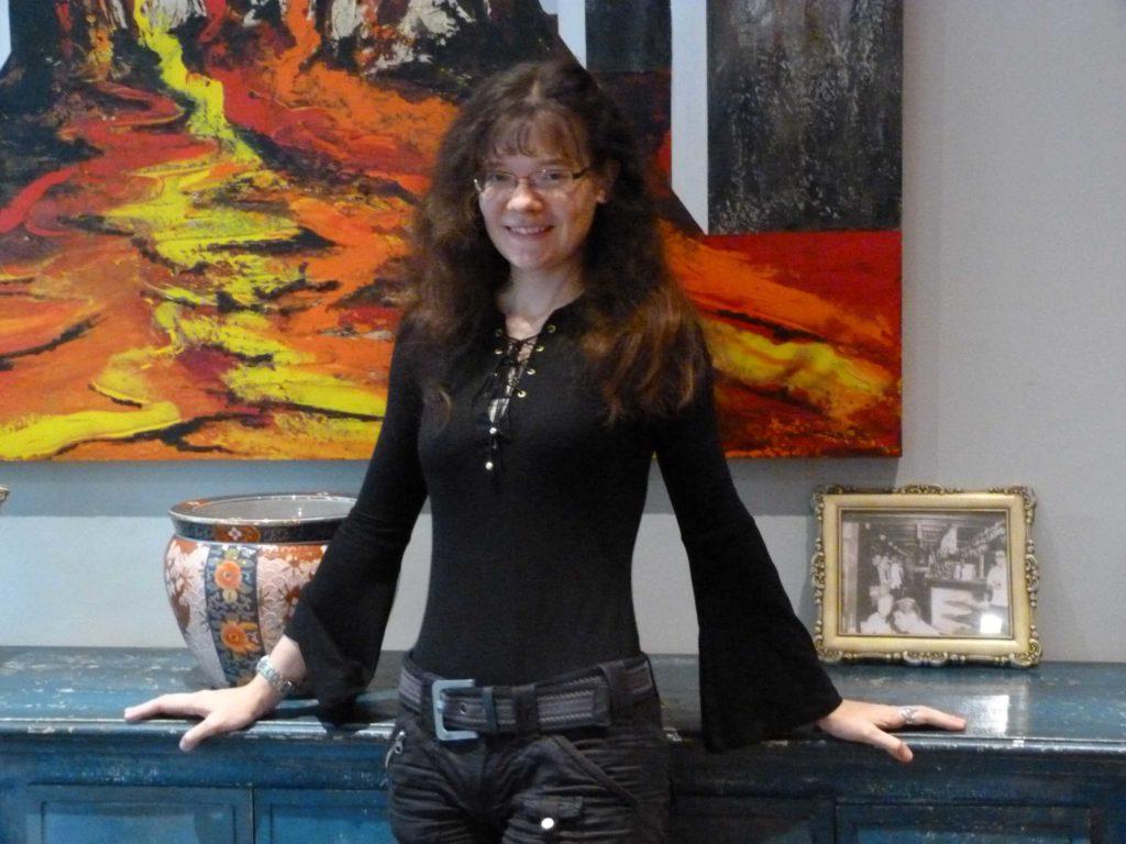 Foto der Autorin, lange rötliche Haare, schlank, schwarzes Top mit Trompetenärmeln
